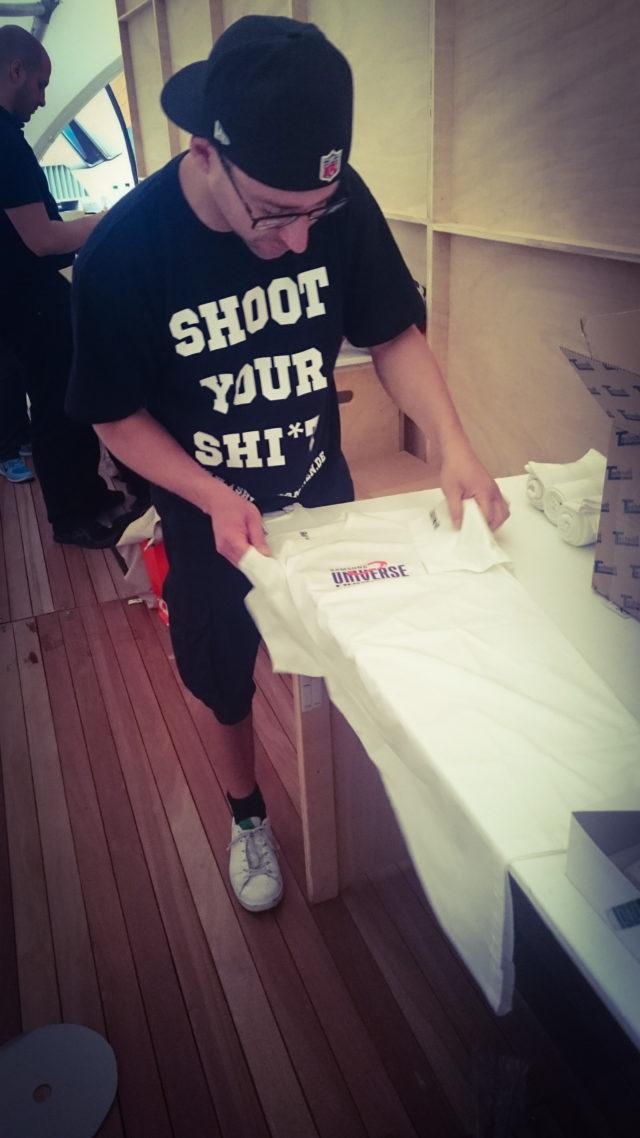 Mario faltet die Shirts mit dem Shoot your Shi*t Klassiker
